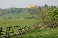 view of Stoke Park showing a broken fence in the foreground, with the Dower House and woodland on the skyline