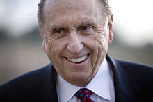 Close-up of older, wrinkled man in conservative suit smiling