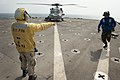 U.S. Navy Seaman Cassandra Collier, left, signals Boatswain's Mate Seaman Alonzo Bender to depart the flight deck after he chocked and chained an MH-60S Knighthawk helicopter aboard the dock landing ship USS 120217-N-KS651-061.jpg