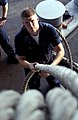 US Navy 030102-N-1397H-002 Seaman Jay Dillon from Kansas City, Miss., assists in restowing the mooring line by guiding it onto the spool.jpg