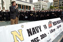 A man in a gray blazer and brown slacks speaks into a microphone behind a banner advertising the 2004 Emerald Bowl. Behind him are a few dozen young men in military uniforms.