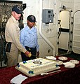 US Navy 061013-N-0191T-008 Chief Mater-at-Arms Edward Stift and Information System Technician Seaman Teri Cotton cut the cake during a ceremony in honor of the Navy's 231st birthday aboard USS San Antonio (LPD 17).jpg