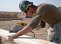 US Navy 080104-N-3857R-006 Steelworker 2nd Class James Branstietter assigned to Naval Mobile Construction Battalion (NMCB) 1, makes a cut on a piece of lumber during the construction of a combat outpost that will be used by the.jpg