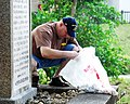 US Navy 090404-N-7843A-021 A Sailor assigned to the mine countermeasures ship USS Guardian (MCM 5) cleans weeds and debris from a memorial honoring residents of Ishigaki, Japan killed in World War II.jpg