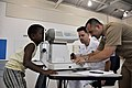 US Navy 090916-N-5740H-528 Hospital Corpsman 3rd Class Matthew Phelps, and Lt. Charles Charbonneau, conducts a vision assessment on a first-grade student.jpg