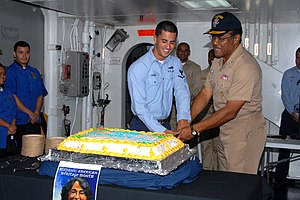 US Navy 091008-N-9761H-041 Vice Adm. D.C. Curtis and Intelligence Specialist 3rd Class Ryan Paigo cut a cake during a ceremony in observance of Hispanic American Heritage Month