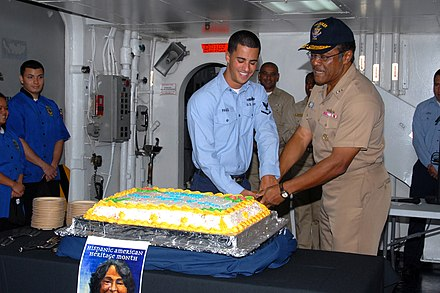 A U.S. Navy vice admiral and an intelligence specialist celebrating Hispanic American Heritage Month in San Diego US Navy 091008-N-9761H-041 Vice Adm. D.C. Curtis and Intelligence Specialist 3rd Class Ryan Paigo cut a cake during a ceremony in observance of Hispanic American Heritage Month.jpg