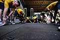 US Navy 110414-N-RC734-654 Sailors and Marines stretch during physical training aboard the amphibious dock landing ship USS Comstock (LSD 45).jpg