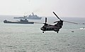 US Navy 120210-N-WI828-006 A CH-46 Sea Knight helicopter flies past the forward-deployed amphibious dock landing ship USS Tortuga (LSD 46) and the.jpg