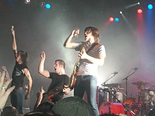 A heavy metal rock band on stage wearing black or white T-shirts and jeans, in the spotlight performing before an audience.