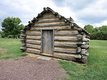 Photograph of a reproduction hut at Valley Forge National Historical Park, Pennsylvania. The hut stands at the site of a recreated brigade encampment along North Outer Line Drive..