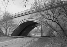 Looking slightly up at a black and white image of a Neoclassical concrete bridge over a road