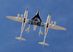 SpaceShipTwo - SpaceShipTwo in a captive flight configuration underneath White Knight Two, during the runway dedication of Spaceport America in October 2010. VMS ''Eve'' is shown carrying VSS ''Enterprise''.