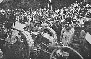Fotografia unei scene din timpul războiului de independență leton din Letonia de Nord, cu o baterie de artilerie plimbată și un steag fluturat din spate.