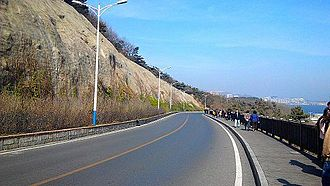 Binhai Road is the main route for Dalian International Walking Festival. View of mountain on one side and sea on the other makes it a popular exercise destination for local people. Bin Hai Zhong Lu Yue 5000Mi (retouched).jpg