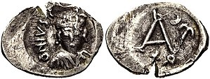 Justin II - 100 nummi coin of Justin II minted in Carthage. Helmeted and cuirass-wearing facing bust, holding shield Monogram; cross above, 100 below.