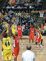 A player in a maize uniform releases a jump shot from the near corner over a defender in an orange uniform with the word Illinois on the front. Other players on both teams box out for a rebound.