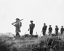 Six evenly spaced Caucasian soldiers wearing slouch hats with their rifles slung march along a dirt road in a straight line from right to left, carrying packs. The camera is at ankle height amidst the grass which is in the foreground, while the men are silhouetted against the skyline.
