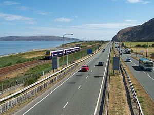 A55 road - An easterly view of the A55 at Penmaenmawr with the North Wales Coast Railway on the seaward side. The Penmaenbach Tunnels are in the distance