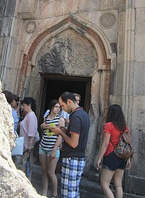 Cultural tourism: tourists outside a Geghard monastery in Armenia, 2015 AYRIVANK MONASTERY 103 (cropped).JPG