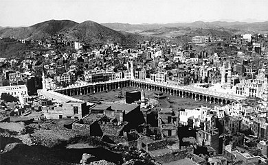 An old photograph showing a black, cubic structure enclosed by rectangular arcade surrounded by buildings and hills