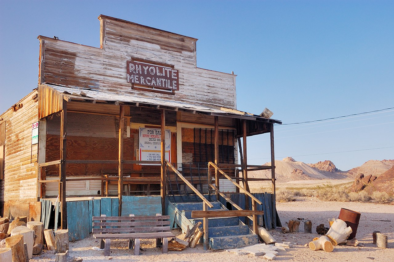 "A small, wooden one-story building with a false second-story front rests on a flat expanse of sparsely-vegetated gravel near some reddish rocks and low hills under a cloudless light-blue sky. A dozen or so sawed logs, a rusting barrel, and a bench for sitting, have been placed here and there in front of the building. A sign on the false front says, ""Rhyolite Mercantile""."