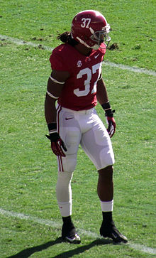 American football player in a crimson jersey and helmet and white pants.