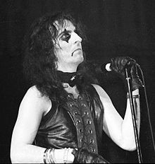 Black-and-white photo of a long-haired man in black makeup with a microphone