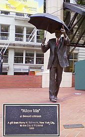 A bronze statue of a man in a business suit; in one hand he is holding an umbrella, while his other arm is extended.
