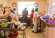 3 trainees dressed in white, cooking with the restaurant's chef who is dressed in black. A young volunteer is taking the food to serve to customers.