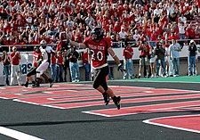 Texas Tech Red Raider football player stands with the a football in the endzone in the foreground with fans in the stands in the background cheering.