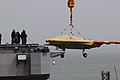 An X-47B is loaded onto flight deck of USS George H.W. Bush. (8720065823).jpg