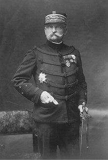 Fotografia monocromática de um homem de bigode, em pé, de frente para a frente, vestindo uma roupa de general, quepe e espada ao lado.