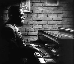 A short-haired black man is sitting behind a piano facing right. He is wearing an opened suit jacket, a white shirt and a necktie. His hands are on the keyboard and he appears to be playing. On the background there is a brick wall on which two paintings or photographs are partly visible.