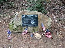 Photo of a memorial plaque fixed to a rock in El Corte de Madera preserve. Multiple small flags of the United States and Australia have been placed in front of it.