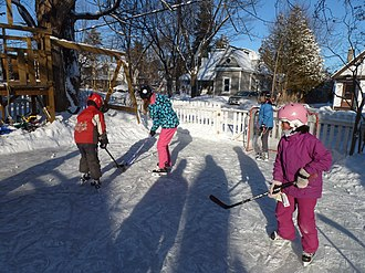 Ice rink - Children playing ice hockey on a backyard rink in Canada