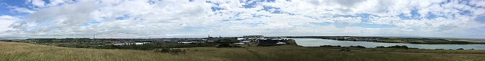 View of Barrow looking south from the Slag Bank including (left to right) Fells of the Lake District, Thorncliffe Crematorium, Ormsgill, Holker Street, Hindpool, St. James' Church, Piel Castle, the Town Hall, BAE Systems Central Yard Facility and Devonshire Dock Hall, the new Barrow Police Station, Furness College, Walney Bridge and Walney Channel, Vickerstown, the Irish Sea, Walney and Ormonde Wind Farms and Barrow/Walney Island Airport