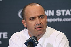 Color head-and-shoulders photograph of bald man (Bill O'Brien) wearing a white sport shirt, and sitting behind a microphone and in front of a navy blue Penn State backdrop.