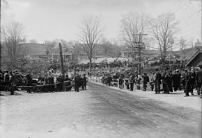 A large group of people observing a road race