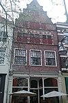 foto van Onderkelderd huis met in zijn huidige vorm in blokken gepleisterde hoge getrapte tuitgevel