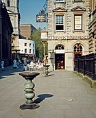 "Two ornate metal pillars with large dishes on top in a paved street, with an eighteenth-century stone building behind, upon which can be seen the words ""Tea Blenders Estabklishec 177-"". People sitting at café-style tables outside. On the right are iron railings."