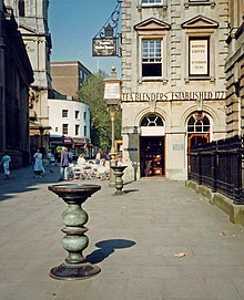 "Two ornate metal pillars with large dishes on top in a paved street, with a eighteenth century stone building behind upon which can be seen the words ""Tea Blenders Estabklishec 177-"". People sitting at cafe style tables outside. On the right iron railings."