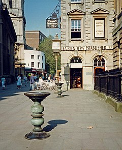 Corn Street, Bristol. A stone-paved pedestrianised street surrounded by classical architecture. In the foreground are two ornate cast bronze tables known as a nails.