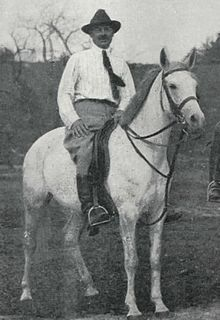 Black and white photo of a man sitting astride a light gray horse