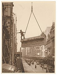 Building labourer on a stone being hoisted up to building, Pitt St, Sydney, c. 1930s, by Sam Hood (4441498235).jpg