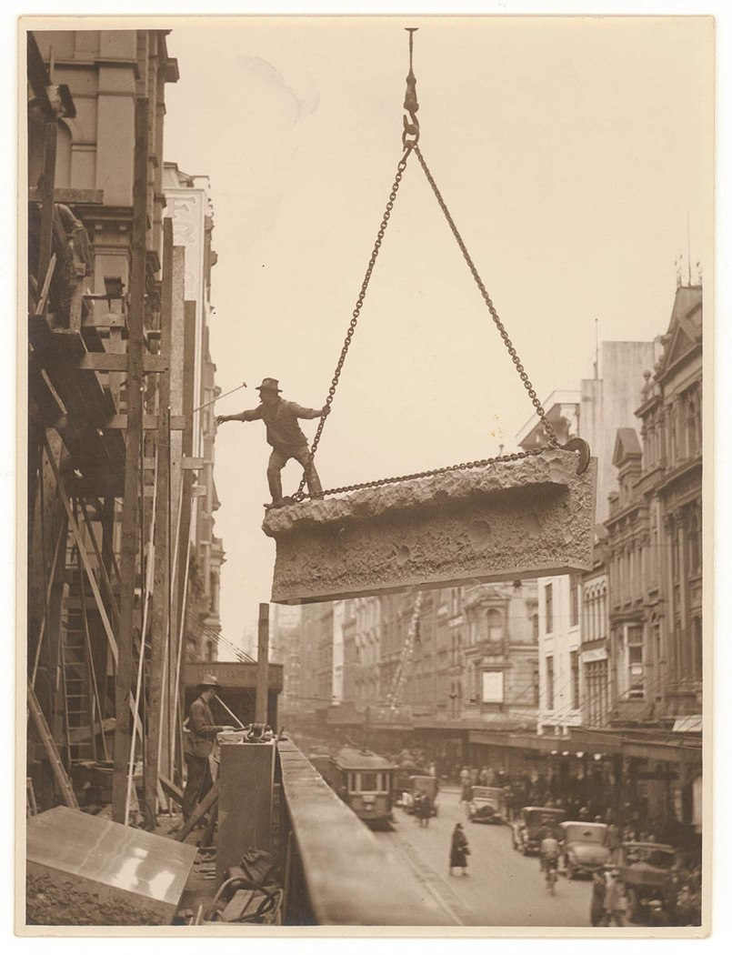 Building labourer on a stone being hoisted up to building, Pitt St, Sydney, c. 1930s, by Sam Hood (4441498235)