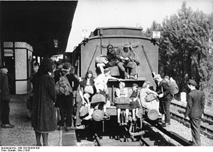 Berlin-Spandau station - Spandau-West station, 1947:  passengers on a crowded train riding on buffers and foot-boards, mostly women foraging for food in the country