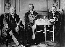 Three men sit around a small table posing for a photograph.