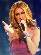 A blonde woman in her early forties holds a microphone with her left hand while she extends her right arm in front of her. She wears a red dress and has diamond bracalets on her wrists.