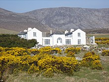 Charles Boycott's house on Achill Island. It is a large white house with two storeys. The mountainous terrain on the island is seen in the background.